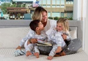 mom reading to her kids on a bed